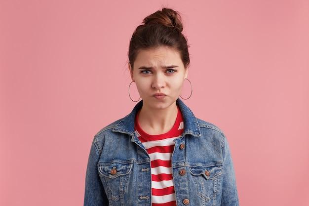 ピンクの壁に隔離された、デニムジャケットの縞模様のtシャツを着て、顔をしかめ、カメラを見て不幸な落ち込んでいるかわいい若い女性。