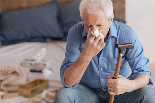 Несчастный подавленный старший мужчина держит трость и использует бумажную салфетку во время слез
