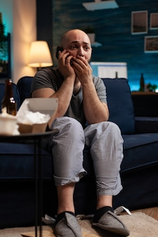 Unhappy depressed shocked man with chronic disease reading tragedy news on smartphone