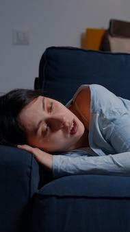 不眠症うつ病の心理的問題に苦しんでソファに横たわって泣いている不幸なうつ病の女性...