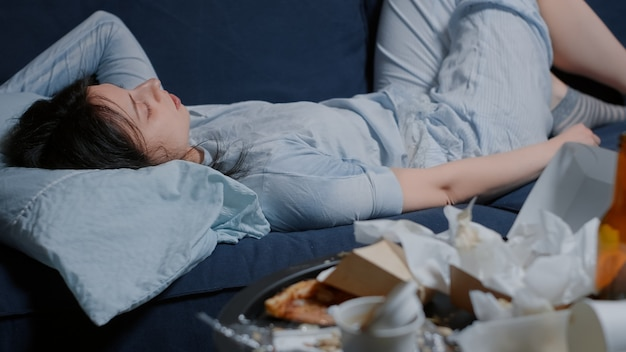 지저분한 테이블에서 길을 잃은 소파에 누워 있는 불행한 우울한 여자
