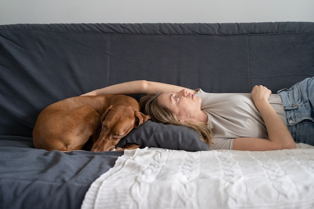 Unhappy depressed woman lying with dog at home on sofa feels apathy has mental problems. loneliness