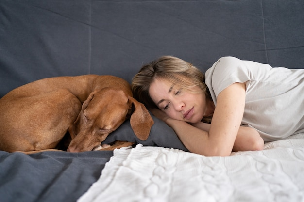 Unhappy depressed woman lying with lovely vizsla dog at home on sofa thinking pondering feels apathy