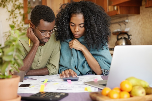 Unhappy and depressed young african-american couple calculating family budget