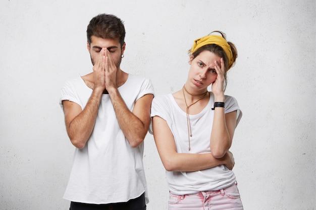 ストレスを感じたり、経済的な問題に直面したり、論争や論争を抱えたりしている不幸な落ち込んでいる若いカップル:女性が額に触れている間に顔を覆っている男性
