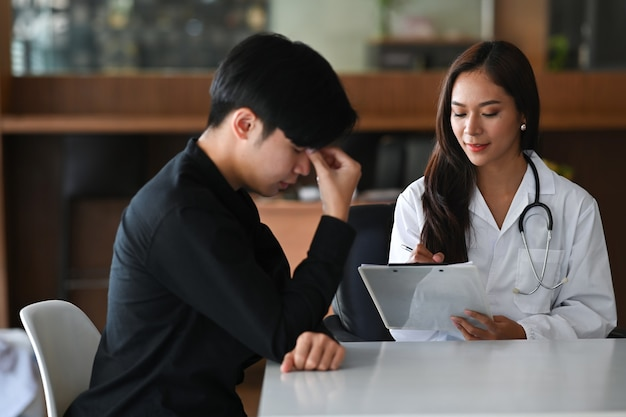Unhappy depressed young man consulting his health problem with female professional psychiatrist doctor.