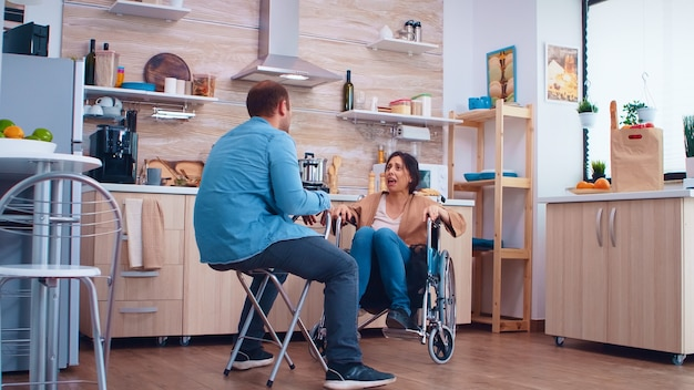 Unhappy disabled wife in wheelchair because of disagreement with husband in kitchen. woman with paralysis handicap disability handicapped difficulties getting help for mobility from love and relations