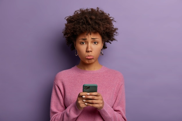 Несчастная разочарованная женщина с афро-волосами, поджимает нижнюю губу, держит смартфон, грустно упускать шанс на хорошую распродажу, расстроена из-за того, что не получает звонок от парня, позирует в помещении, одетая небрежно