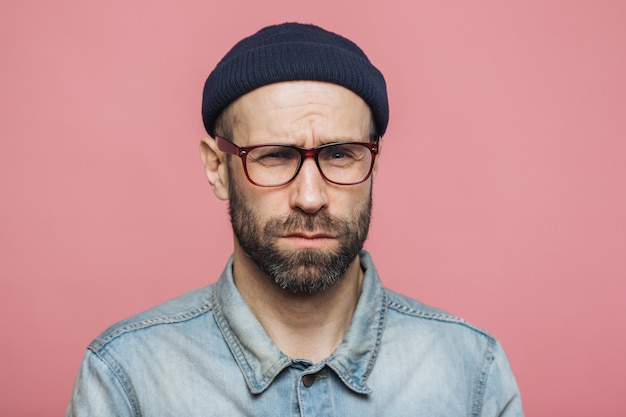 Unhappy discontent unshaven male looks with grumpy expression, wears glasses black hat