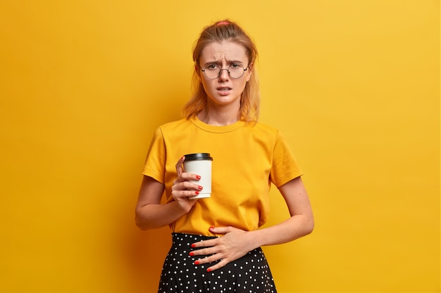 Unhappy displeased female frowns face, feels unwell, keeps hand on belly, drinks takeaway coffee, ate spoiled food, wears transparent glasses, casual yellow t shirt