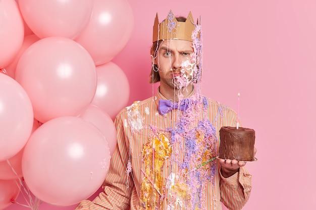 不幸な不機嫌な男は顔を眉をひそめ、正面を怒ってケーキを保持し、膨らんだ風船は眉を上げ、ピンクの壁に隔離された誕生日で友人を祝福します