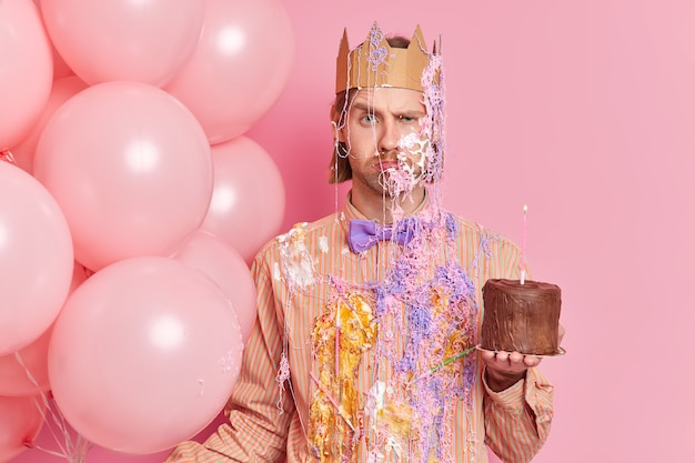 Unhappy displeased man frowns face looks angrily at front holds cake and inflated balloons raises eyebrows going to congratulate friend with birthday isolated over pink wall