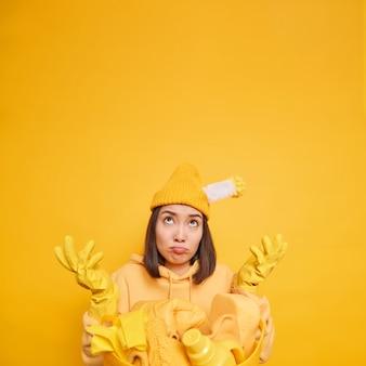洗濯をしているために疲れ果てている不幸な不機嫌な疲れた女性は、黄色い壁の上にさりげなく隔離された服を着て上向きに焦点を合わせた手のひらを広げます
