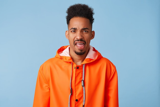 Unhappy displeased young african american dark skinned boy wears in orange rain coat, gestures indoor, frowns face with aversion. stands.