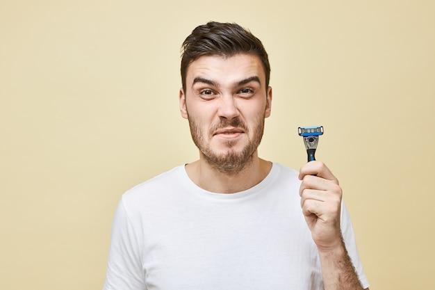 剛毛の顔をゆがめた不幸な不機嫌な若いブルネットの男は、彼のひげを剃りたくない、剃るプロセスを嫌う、敏感肌を持っている、かみそりで孤立したポーズを手に