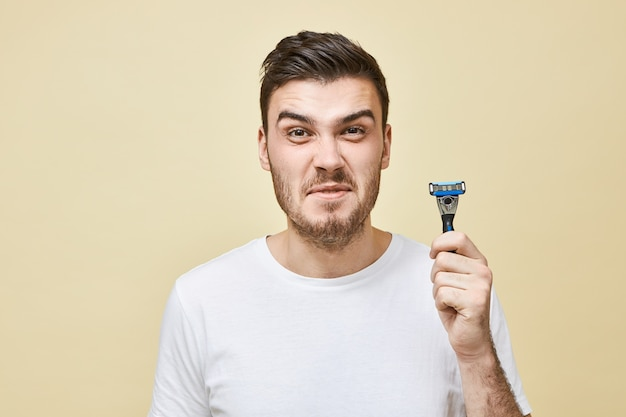 Unhappy displeased young brunette man with bristle grimacing does not want to shave his beard, hating shaving process, having sensitive skin, posing isolated with razor in hands