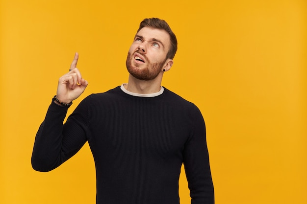 Unhappy displeased young man with beard in black longsleeve looks irritated and pointing up to copyspace over yellow wall
