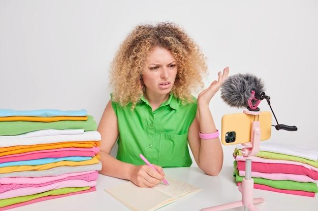 곱슬머리를 한 불만족스러운 여성이 노트북에 몇 가지 정보를 적었다