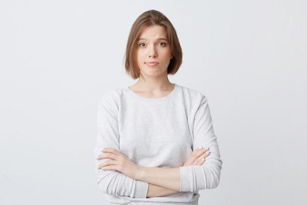 Несчастная недовольная молодая женщина в лонгсливе стоит со сложенными руками