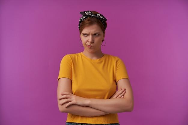 머리에 머리띠가 달린 노란색 티셔츠에 불행한 불만족 된 젊은 여성이 불쾌 해 보이고 팔이 자주색 벽을 넘어 계속 유지됩니다.