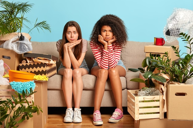 Unhappy diverse young women sit on sofa, tired after changing place of living, have to unpack belongings from boxes, pose in messy room, have new home, look sadly. moving day concept