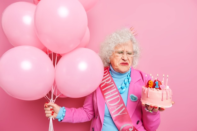 Unhappy elderly beautiful woman sad about getting older looks at delicious cake with burning candles celebrates 91st birthday hollds bunch of balloons accepts congratulations on party. aging concept