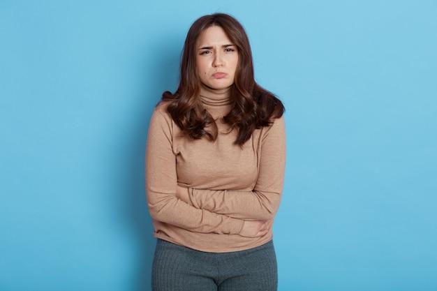 Несчастная европейская темноволосая женщина трогает живот, у нее спазмы во время менструации