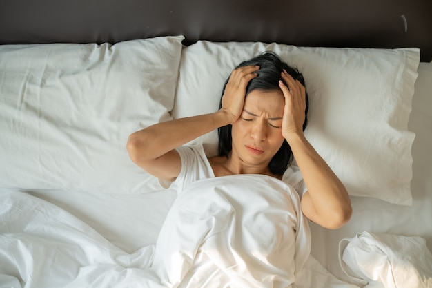 Unhappy exhausted mature woman with closed eyes lying in bed, touching temples close up, tired female suffering from headache or migraine, feeling unwell, suffering from insomnia, lack of sleep