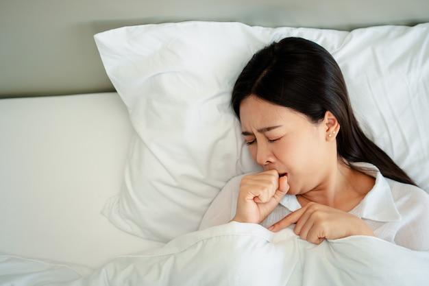 不幸な疲れ果てた女性がベッドに横たわって目を閉じた頭痛の原因喉の痛みと疲れた