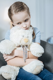 Unhappy fair-haired blue-eyed little girl thinking and holding her teddy bear while sitting in the armchair