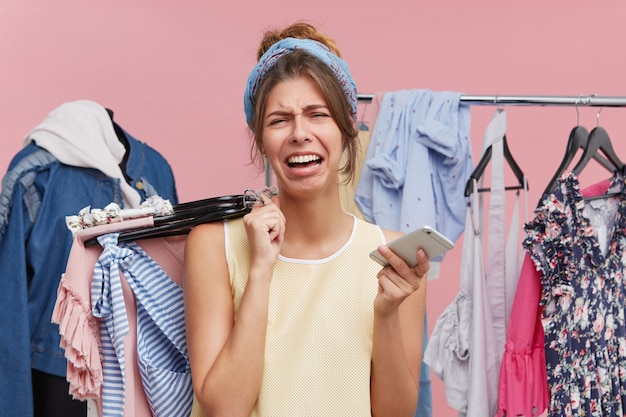 Unhappy female going to cry while standing in shopping centre, holding in one hand hangers with clothes and in other mobile phone, having no money on her account to pay for clothes. style and clothes