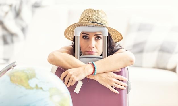 불행한 여성 여행자는 여행 제한 때문에 필사적으로 보이는 지구 옆에 가방을 놓고 있습니다.