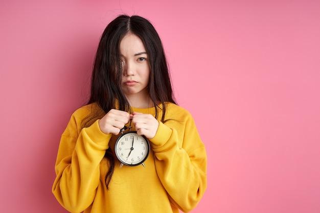 손에 알람 시계가있는 불행한 여성은 아침에 잠이 필요하고 슬픔으로 카메라를 봅니다. 분홍색 배경에 고립