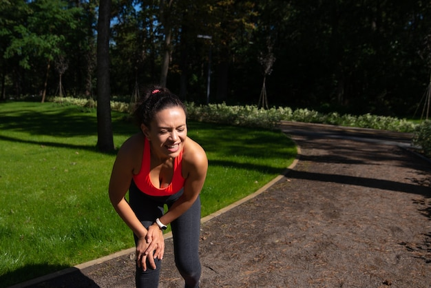 An unhappy fit woman feeling pain in her knee during sport and workout outdoor