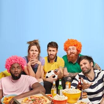 Недовольные четверо мужчин и одна женщина недовольны финальным результатом футбольного матча, расстроенная любимая команда проиграла игру