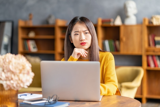 Unhappy frowning asian woman forgetting smth working on laptop
