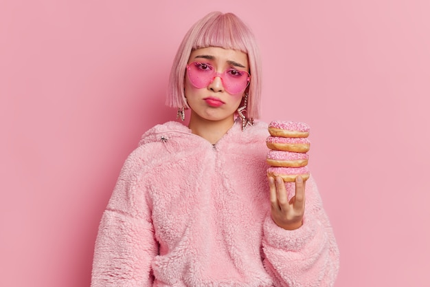 ボブの髪型をした不幸な欲求不満のアジア人女性は、毛皮のコートとサングラスを着てダイエットを続けると、おいしいドーナツの山を抱えて悲しむ