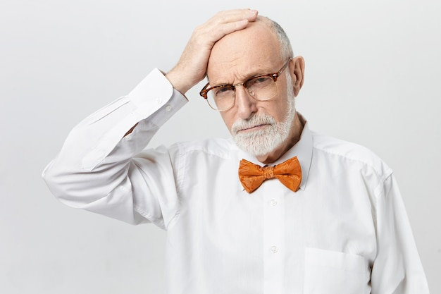Unhappy frustrated caucasian male pensioner with thick beard suffering from memory loss problem posing, rubbing his bald head, having depressed stressed facial expression, frowning