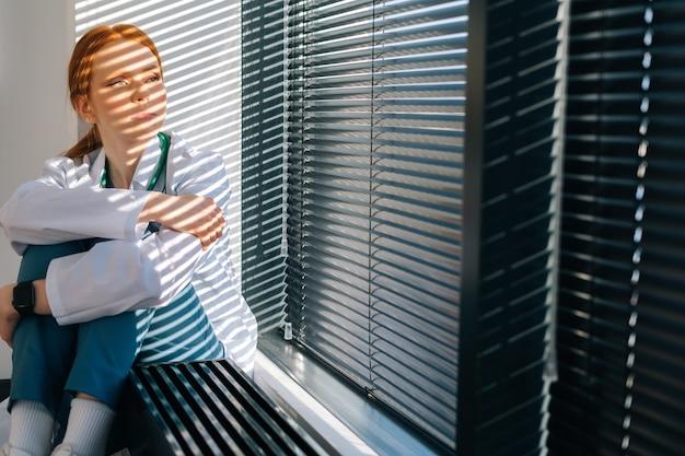 화창한 날 창가에 앉아 울고 있는 불행한 여성 의사. 스트레스를 받은 젊은 여성 의사는 직업상의 과실에 대해 걱정하고 있습니다. .