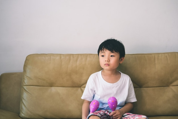 Unhappy frustrated little boy siting on sofa at home.