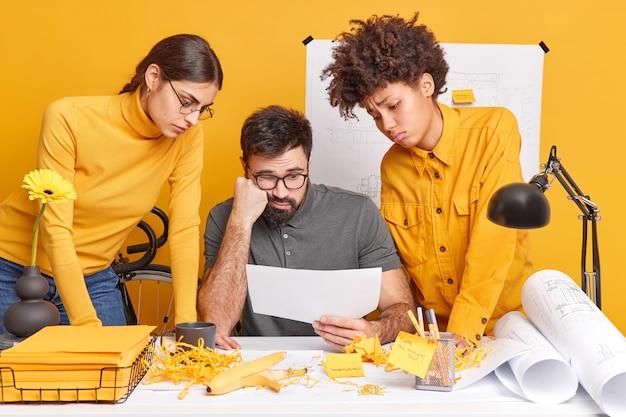 Недовольные и разочарованные три многонациональных профессиональных дизайнера позируют за рабочим столом, обсуждают новые идеи, сконцентрированные на бумаге, рисуют чертежи зданий, проверяют эскизы интерьера.