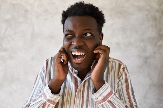 縞模様のシャツを着た不幸な欲求不満の若いアフリカ系アメリカ人男性