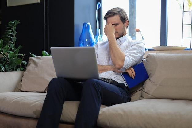 소파에 노트북과 함께 앉아 손으로 머리를 잡고 불행 좌절된 젊은 남성.