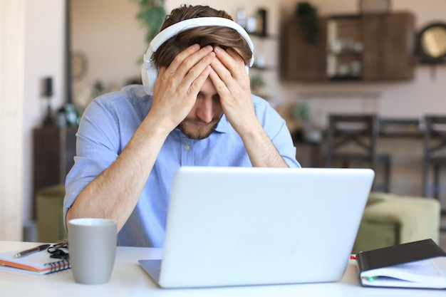 Несчастный разочарованный молодой мужчина держит голову руками, сидя с ноутбуком за столом у себя дома.