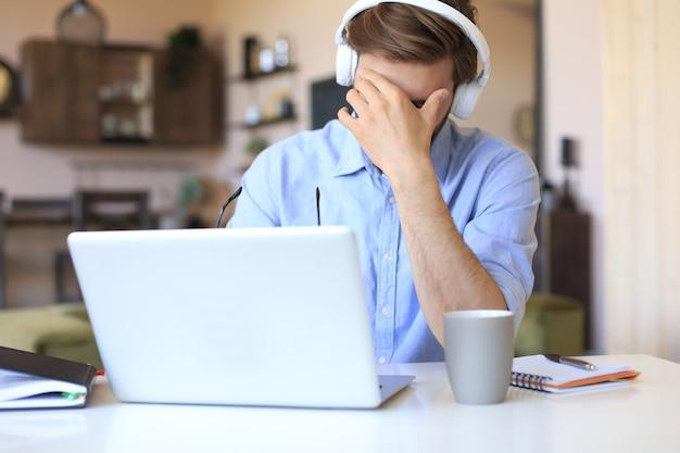 집에서 책상 뒤에 노트북과 함께 앉아 손으로 머리를 잡고 불행 좌절된 젊은 남성.