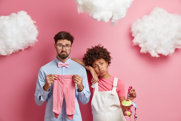 Unhappy future parents await for baby pose with necessary items for newborn child pose together against pink wall. displeased pregnant woman leans at shoulder of husband holds mobile toy