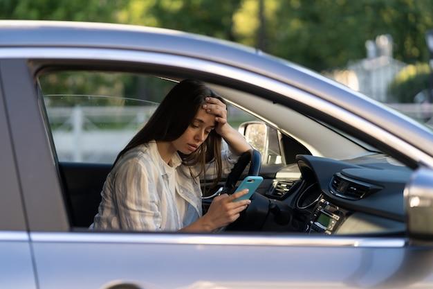 不幸な少女がスマートフォンでsmsメッセージを読んで泣く車を運転して動揺している女性が彼氏と別れる