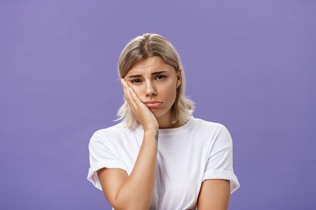 Несчастная девушка, положив лицо на ладонь и хмурясь от разочарования и сожаления