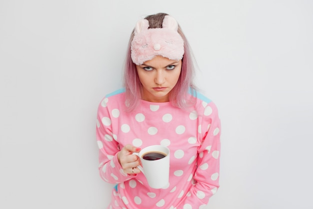 Unhappy girl slept badly. portrait of grumpy woman in pink pyjamas.