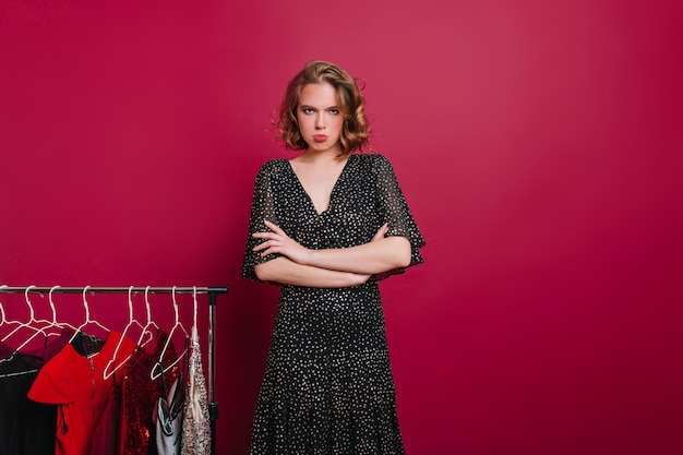 Unhappy girl standing on claret background with arms crossed near hangers with dresses